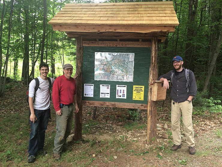 Three hikers next to trail kiosk