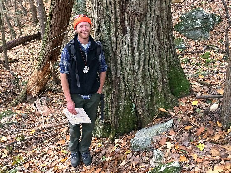 Sam Perron standing next to a big red oak tree