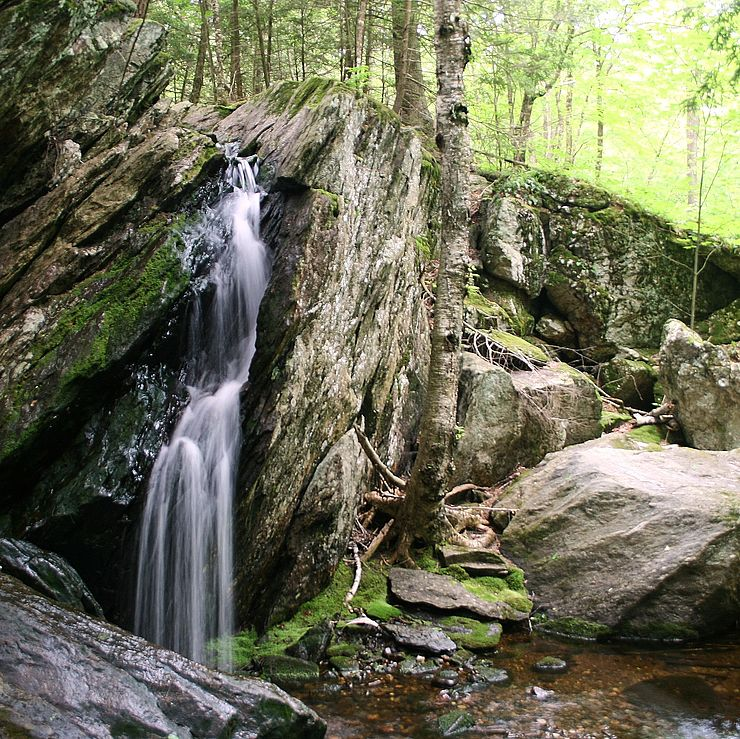 Small waterfall cascading from large glacial boulders